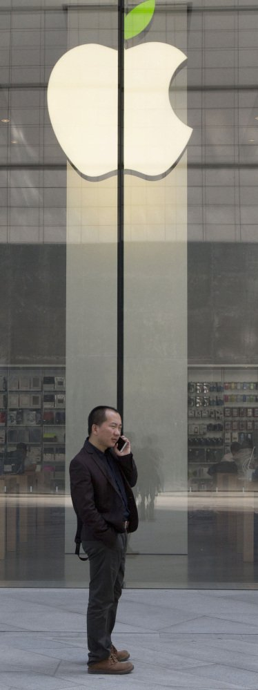 A man uses his phone near an Apple store in Beijing. Since a record close at $133 on Feb. 23, Apple has slumped to $115.40.