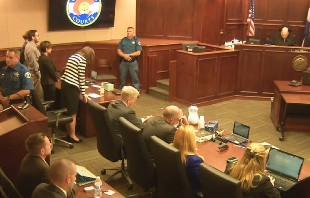 In this image made from Colorado Judicial Department video, Defense Attorney Tamara Brady, at left in stripped suit, leans into the defense table as Judge Carlos A. Samour Jr. reads the jury's sentencing verdict Friday in the Colorado theater shooting trial. James Holmes, top left in tan shirt, will be sentenced to life in prison without parole because the jury could not agree that he should get the death penalty.
