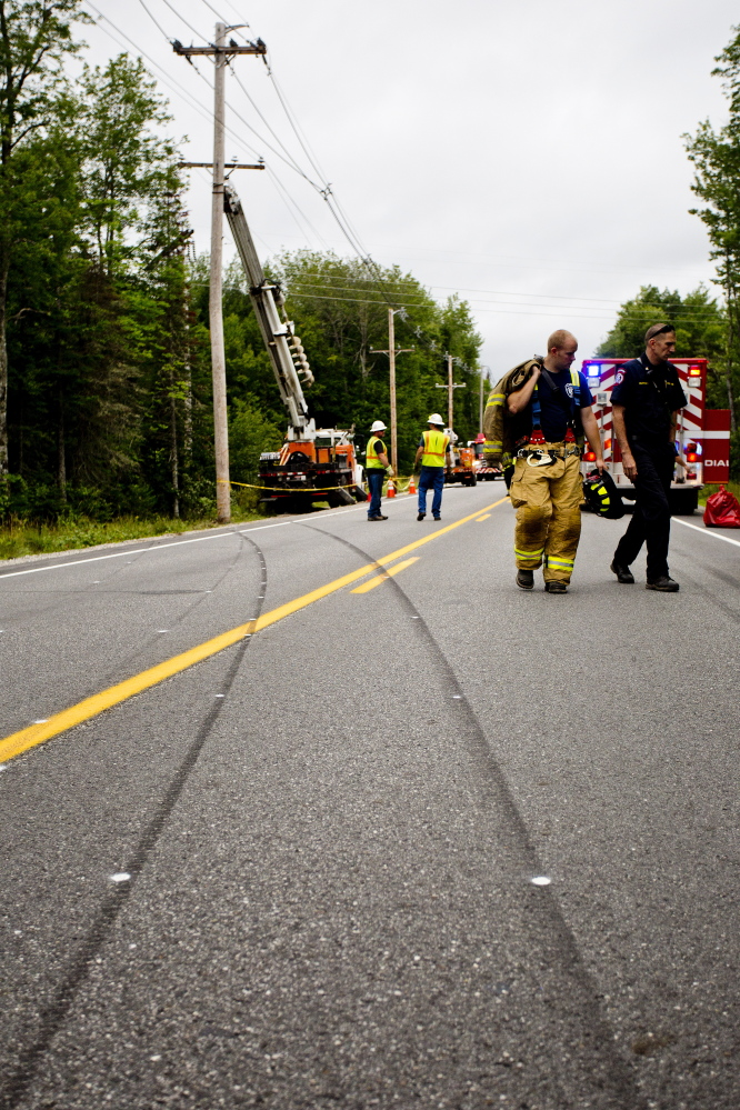 Emergency personnel walk past tire skid marks that lead straight to the utility pole that a vehicle struck while traveling on Route 11 in Casco on Tuesday morning.