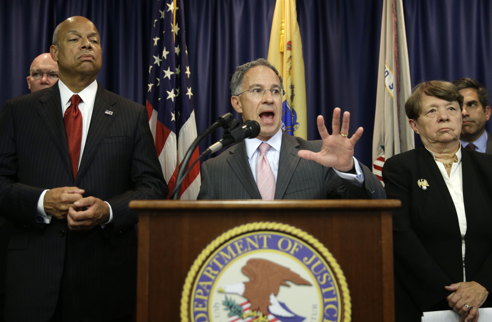 U.S. Attorney Paul Fishman of  New Jersey, center, speaks during a news conference in Newark, N.J., on Tuesday about a scheme carried out by an international group of hackers and stock traders who made $30 million by breaking into the computers of corporate newswire services.