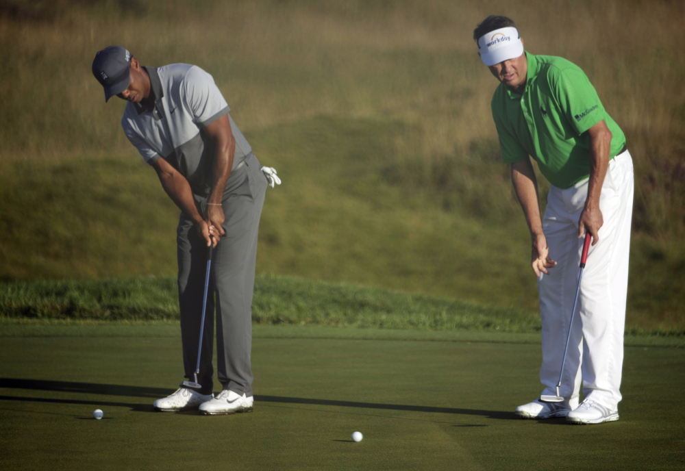 Tiger Woods, left, and Davis Love III practice putting Tuesday for the PGA Championship  at Haven, Wis. Woods' winless streak in major tournaments is at 23, dating back to his winning the U.S Open in 2008.