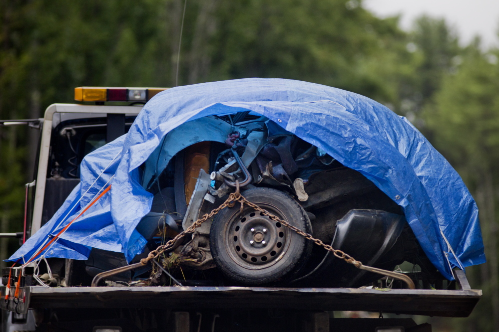 The mangled remains of the front of a vehicle that struck a telephone pole on Route 11 on August 11, are towed away from the scene.  Gabe Souza/Staff Photographer