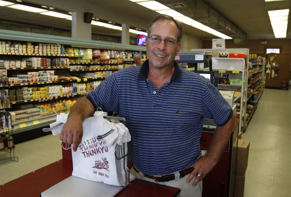 South Portland grocer Alan Cardinal acknowledges it's not ideal to suddenly charge customers for use of bags, but says the environmental concerns are legitimate. Joel Page/Staff Photographer