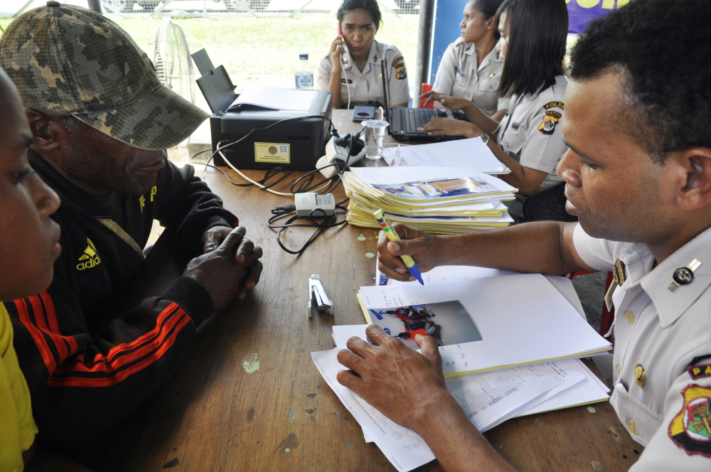 Relatives of passengers on the Trigana Air Service flight listen to a National Policies Disaster Victim Identification official at Sentani airport in Jayapura, Papua province, Indonesia, on Monday.