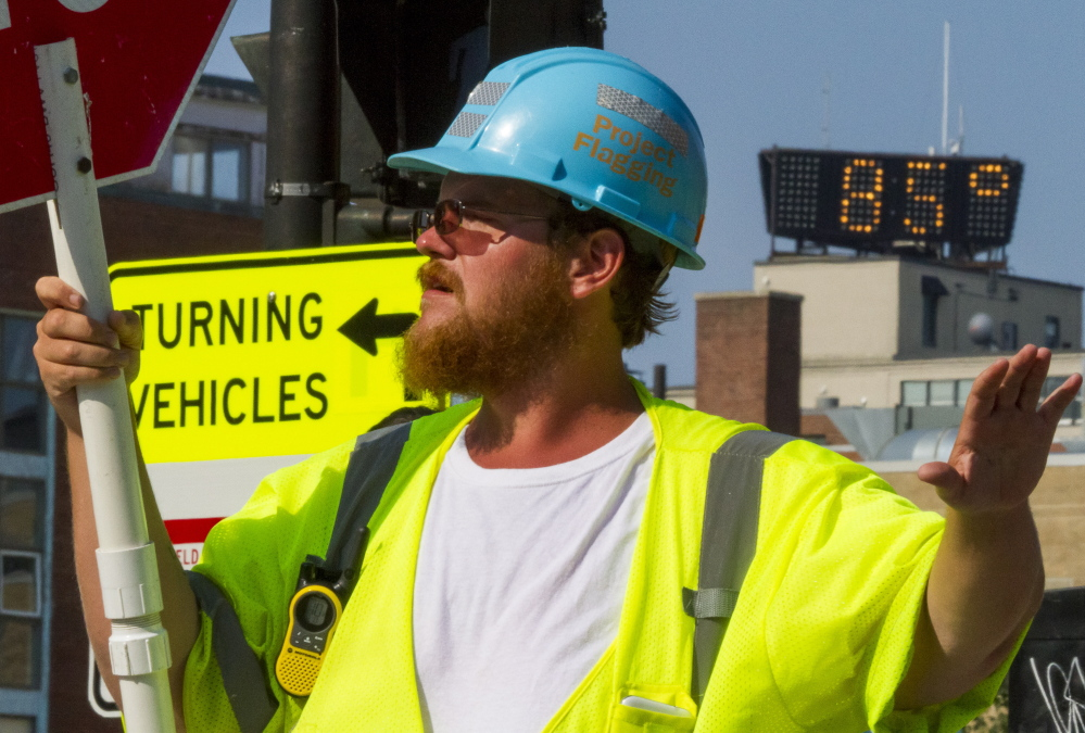 Construction flagger Michael Merrifield directs traffic at the intersection of High and Spring streets Monday, when temperatures hit a high of 89 in Portland. Ozone levels reached unhealthy levels for the first time in two years, state environmental officials said.