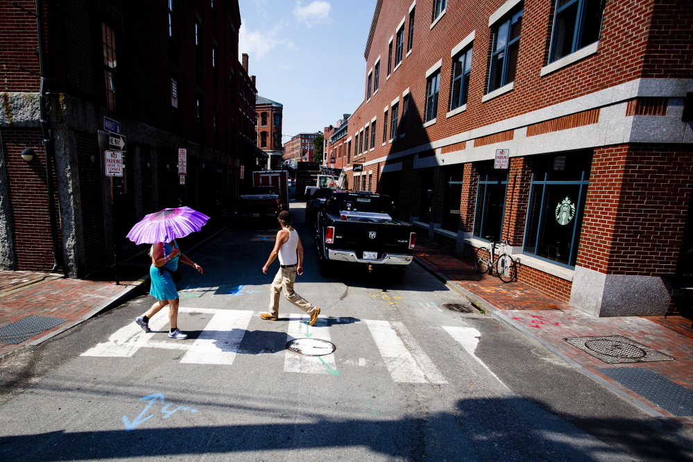A woman uses an umbrella to keep the sun off as she tries to beat the heat on Commercial Street in Portland on Monday.