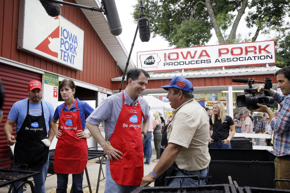 The Associated Press Republican presidential candidate Wisconsin Gov. Scott Walker talks with Dana Wanken, right, before working the grill at the Iowa Pork Producers tent during a visit to the Iowa State Fair on Monday in Des Moines, Iowa, where he talked about immigration.