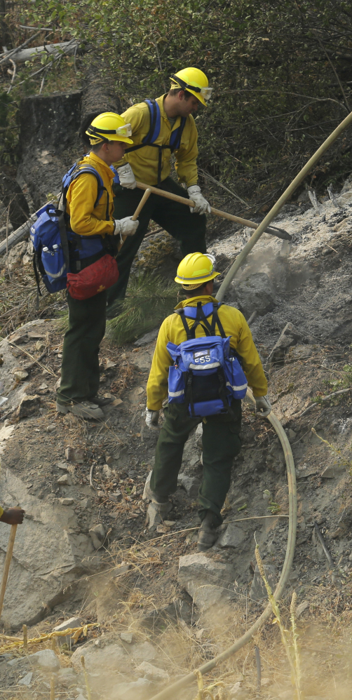 Firefighters and Washington National Guard soldiers work Wednesday to extinguish hot spots near Chelan, Wash.