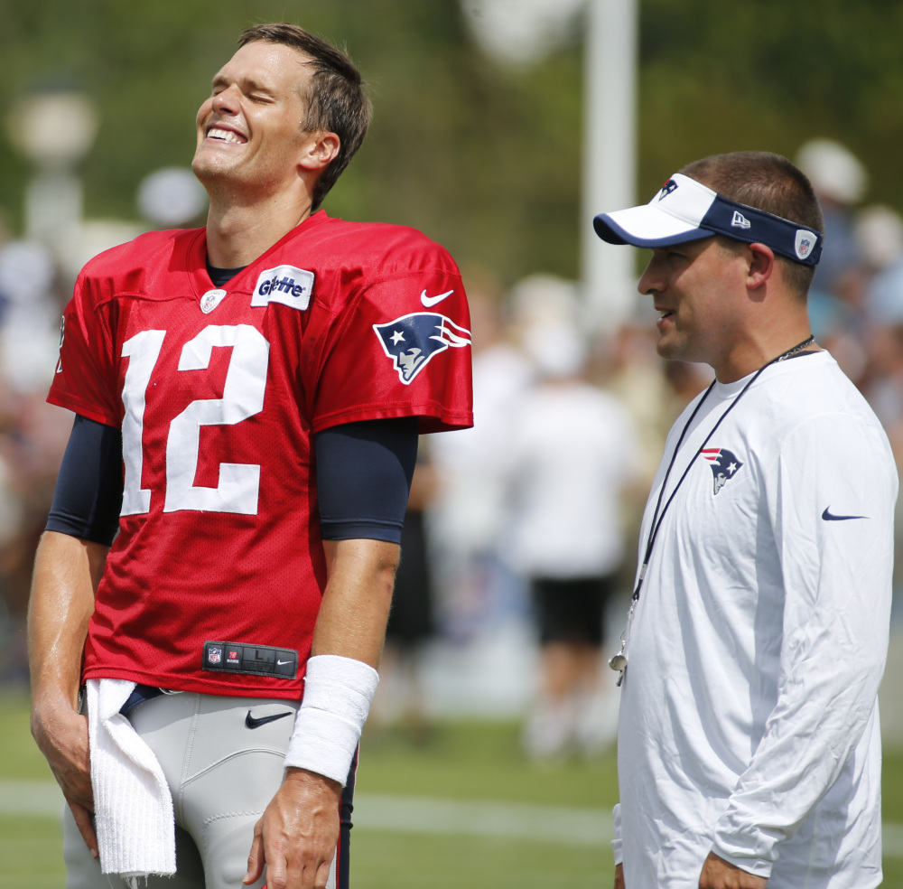 Patriots quarterback Tom Brady shares a laugh with offensive coordinator Josh McDaniels during a joint practice Thursday with the New Orleans Saints.