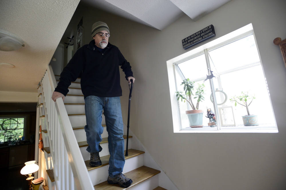 Bob Sprankle struggles to navigate the stairs at his home in Portsmouth, N.H. The 52-year-old former Wells Elementary School teacher used to run 4 miles a day, but now is largely confined to his home. His applications for disability were denied, but he lives with too much pain to work, so he lost his $71,000 salary as well.