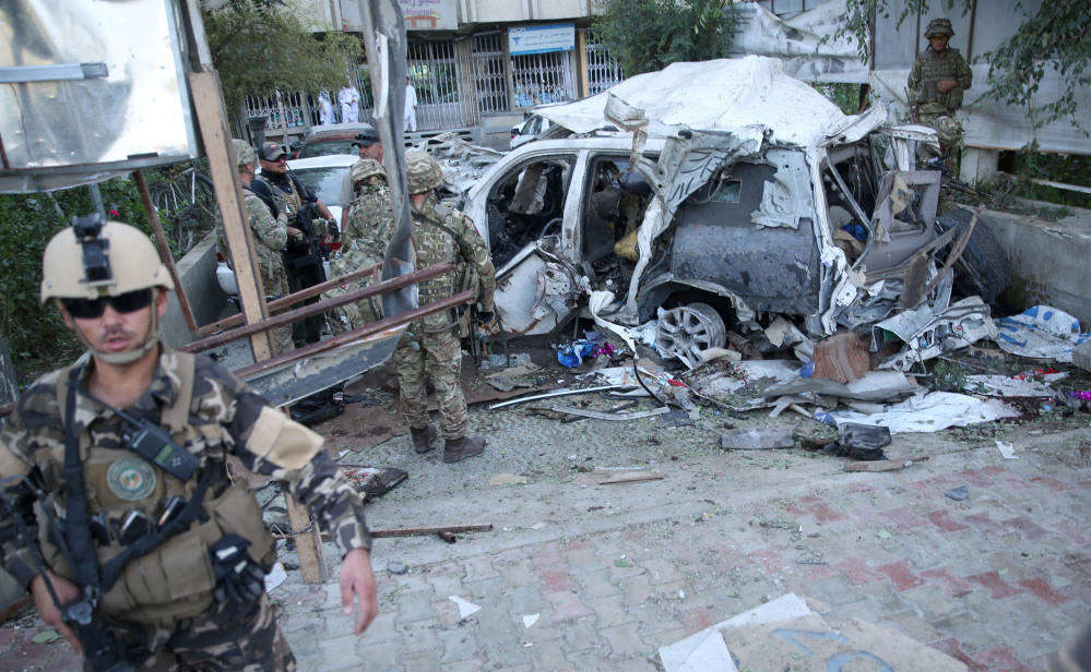 Afghan security forces and British soldiers inspect the site of a suicide attack in the heart of Kabul, Afghanistan, on Saturday. The car bomber attacked a NATO convoy traveling through a crowded neighborhood in Afghanistan's capital Saturday, killing at least 10 people, including Corey Dodge of Garland, and two other NATO contractors.