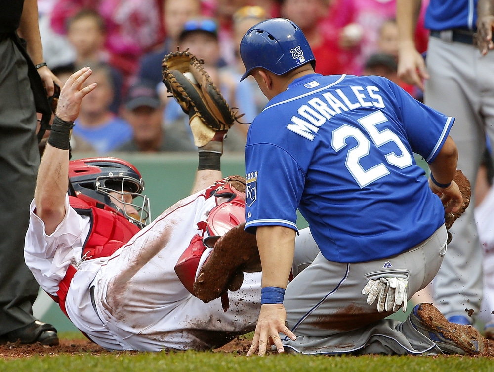 Boston Red Sox catcher Ryan Hanigan falls backward after tagging out Kansas City Royals' Kendrys Morales in the ninth inning of Boston's 8-6 loss Sunday at Fenway Park in Boston.