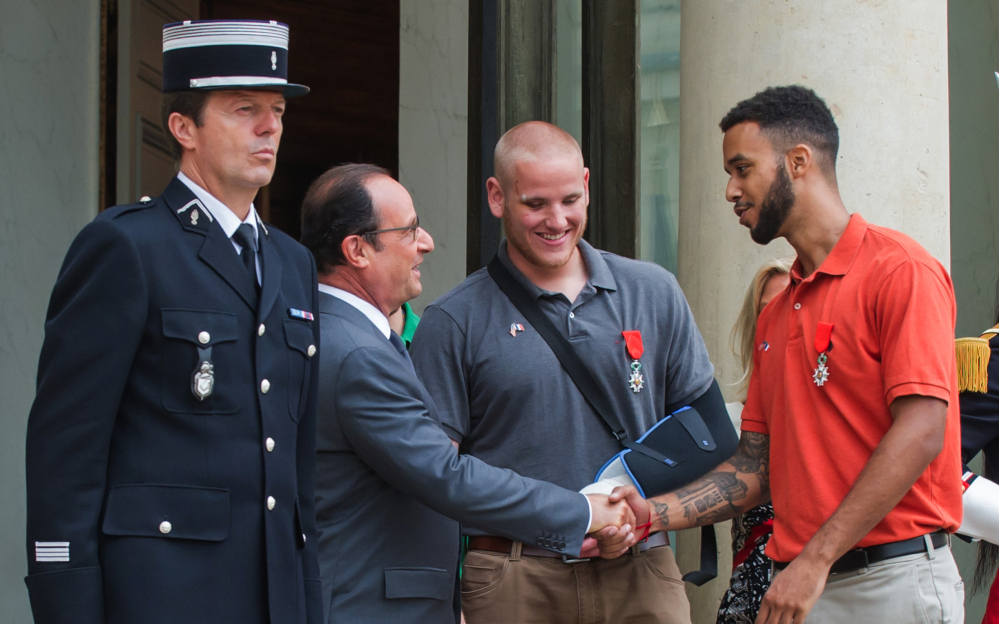 French President Francois Hollande shakes hands with Anthony Sadler, a senior at Sacramento State University in California, while Airman Spencer Stone looks on as they leave the Elysee Palace after Hollande awarded them the Legion of Honor on Monday.