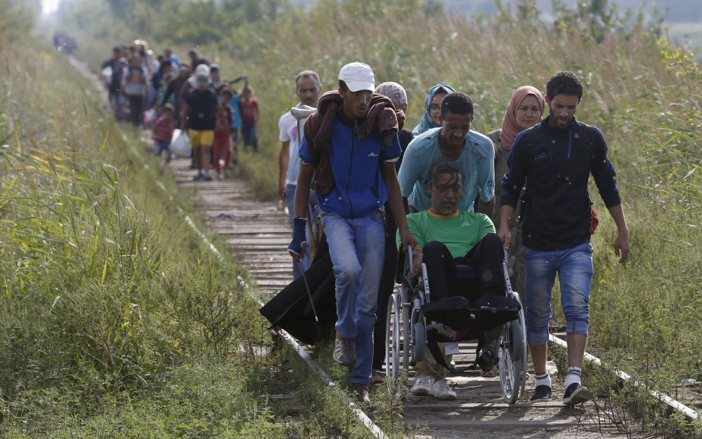 Migrants assist a wheelchair user as they traverse a railway track near the Serbian border with Hungary, near Horgos, Serbia, on Tuesday. A new wave of people fleeing war-torn countries in the Middle East and Africa is straining resources in some European countries.