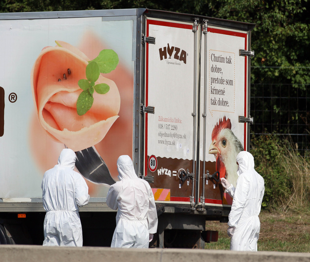 Investigators stand near a  truck that  stands on the shoulder of the highway A4 near Parndorf south of Vienna, Austria, Thursday, Aug 27, 2015. At least 20 migrants were found dead in the truck parked on the Austrian highway leading from the Hungarian border, police said.