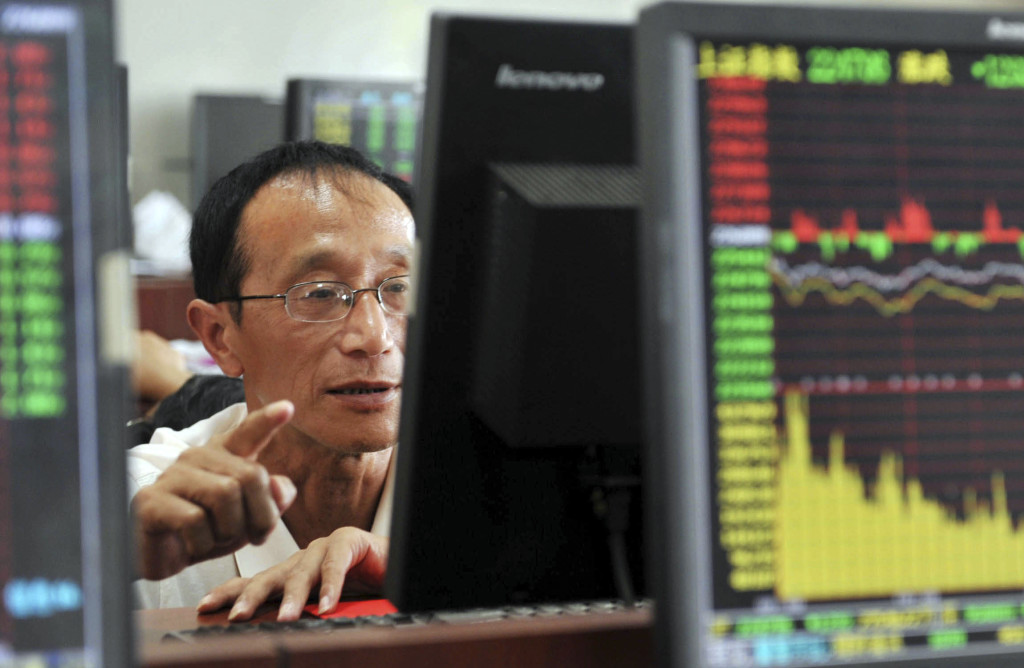 A Chinese stock investor monitors stock prices at a brokerage house in Hangzhou in eastern China's Zhejiang province Tuesday . China's stock market index tumbled for a fourth day, falling 7.6 percent Tuesday to an eight-month low. Chinatopix via AP