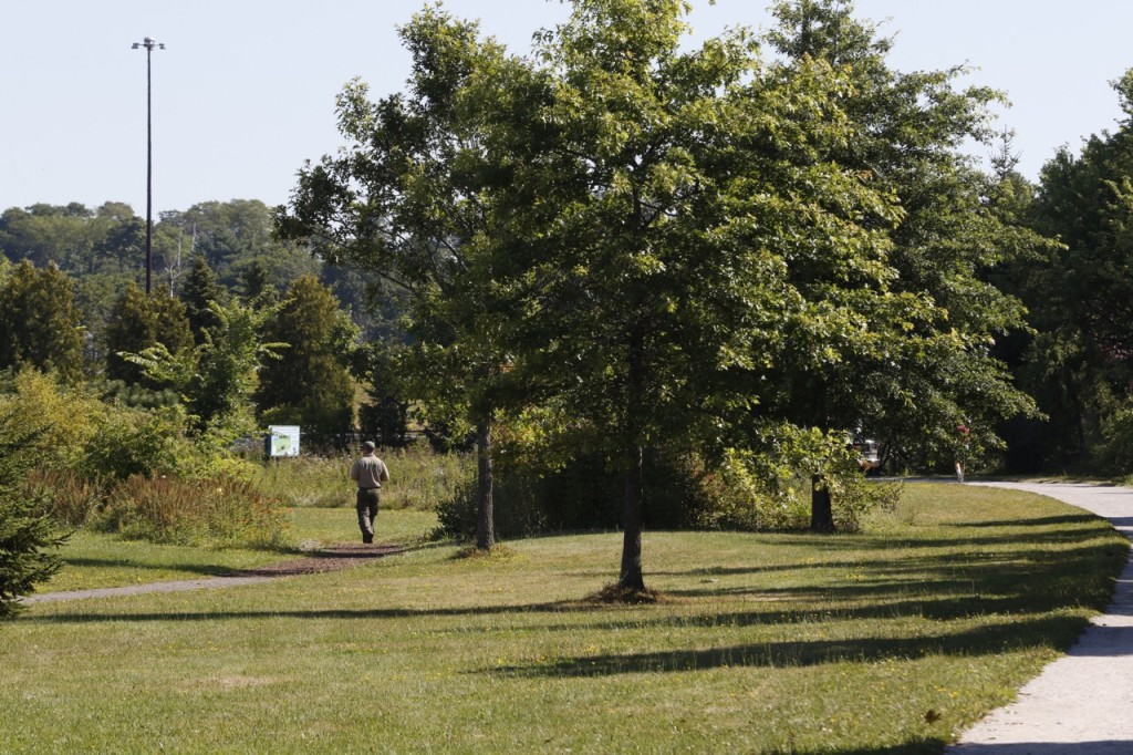 A park ranger walks along the Back Bay Cove trail Thursday, Aug. 13, 2015 in Portland, Maine near the the scene of a reported sexual assault.