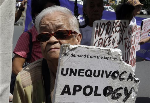 "Remedios Tecson, 85, a Filipino ""comfort woman"" during World War II, displays a placard as she joins a rally outside the Japanese Embassy in Manila ahead of the statement by Japanese Prime Minister Shinzo Abe marking the 70th annivesary of Japan's surrender Friday. The Associated Press"