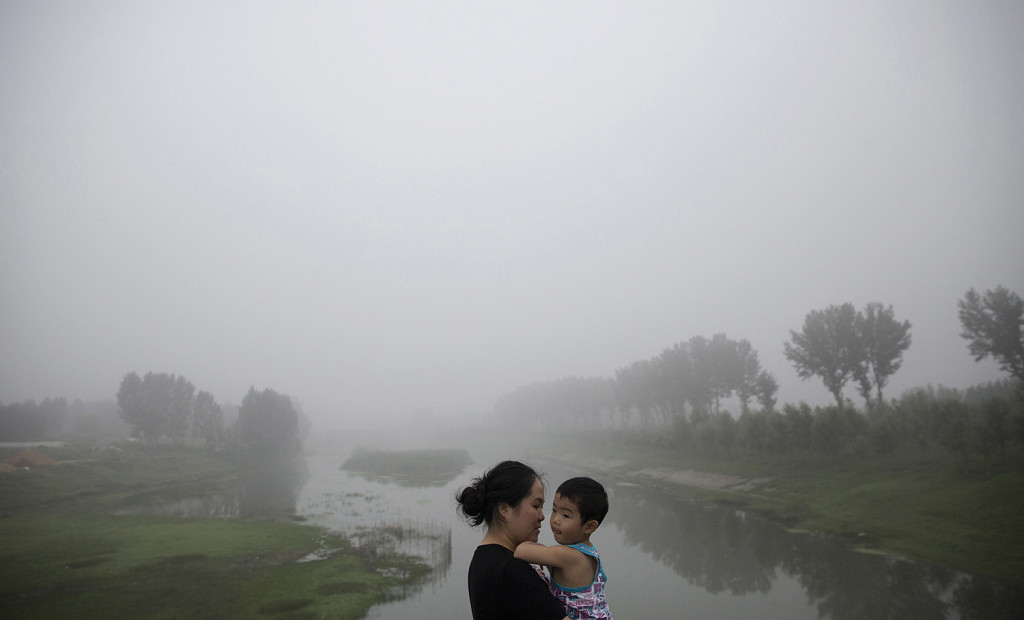 This woman and child are among travelers waiting for the highway from Beijing to China's Hebei Province to be reopened after it was closed for low visibility from heavy air pollution last week.