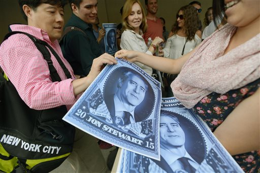 """People waiting in line for the taping of Jon Stewart's final episode of """"The Daily Show"""" receive posters of the comedian. Viorel Florescu/The Record of Bergen County via The Associated Press"""