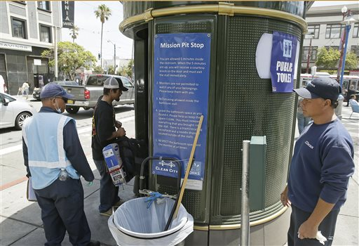 An attendant looks on as a man enters a Pit Stop public toilet outside a Mission District transit station in San Francisco recently. The Pit Stop, located by a public wall covered with a repellant paint that makes pee spray back on the offender, is a project operated by San Francisco Public Works that provides portable toilets and sinks and is part of the city's latest attempt to clean up urine-soaked alleyways and walls. The Associated Press