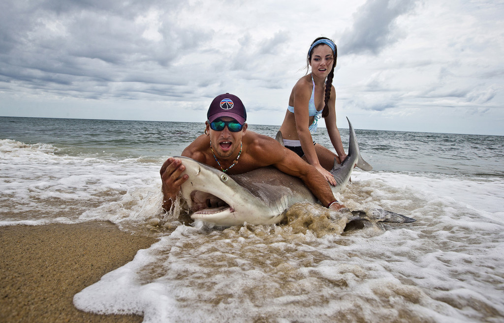 Elliot Sudal catches a brown shark off the beach in Siasconset, on Nantucket. Standish native Marisa Butler helps him measure and tag the sharks before they are released. Boston Globe staff photo by Stan Grossfeld