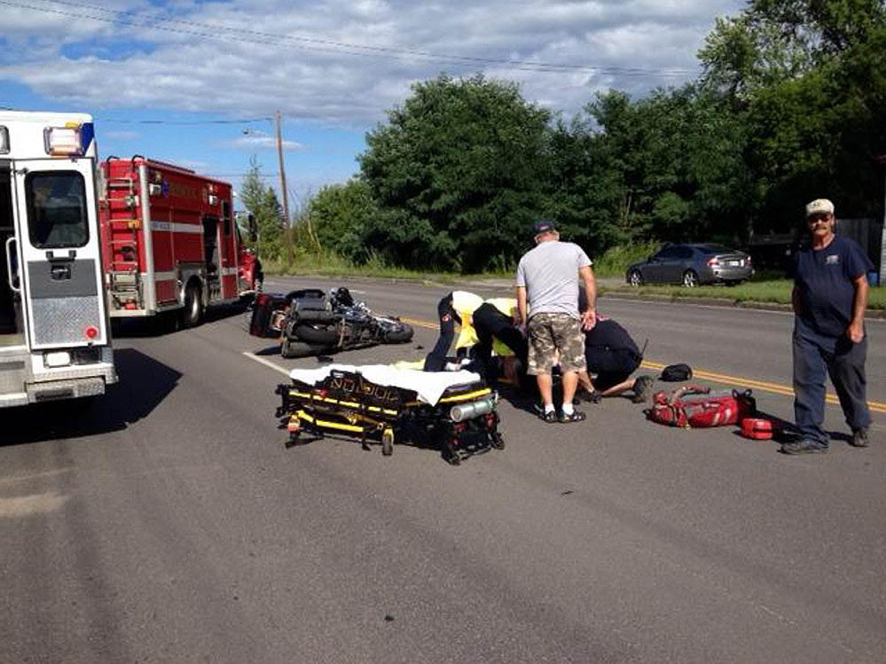 Emergency responders help a motorcyclist who was injured in a collision with a Jeep on College Avenue Thursday afternoon in Waterville. Staff photo by Amy Calder