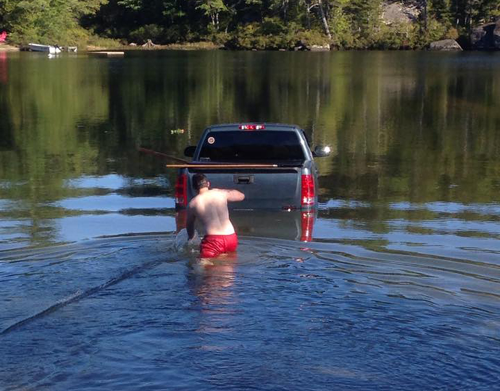 A man wades out to his truck after it rolls into Branch Lake near Ellsworth with his dog inside the cab.