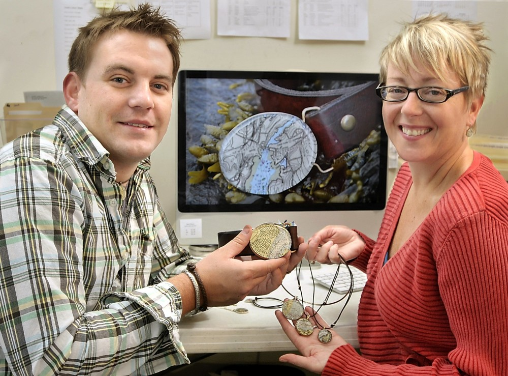 Gordon Chibroski/Staff Photographer John Guptill and Charlotte Leavitt of Chart Metalworks with some of their jewelry creations fashioned from cutouts of nautical charts.