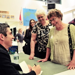 Blanco signs books following his talk for Bailey Public Library trustees Elizabeth Sienko, Mary Jane Auns and Winthrop Town Council Chairwoman Sarah Fuller.