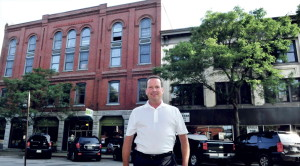 Bill Mitchell stands between the two buildings he now owns on Common Street in Waterville, which he plans to fix up and lease for a restaurant, businesses and office space.