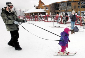 Gabbie Archibald learns to ski with help from her father Ian beside the renovated base lodge at Saddleback ski resort in 2009.