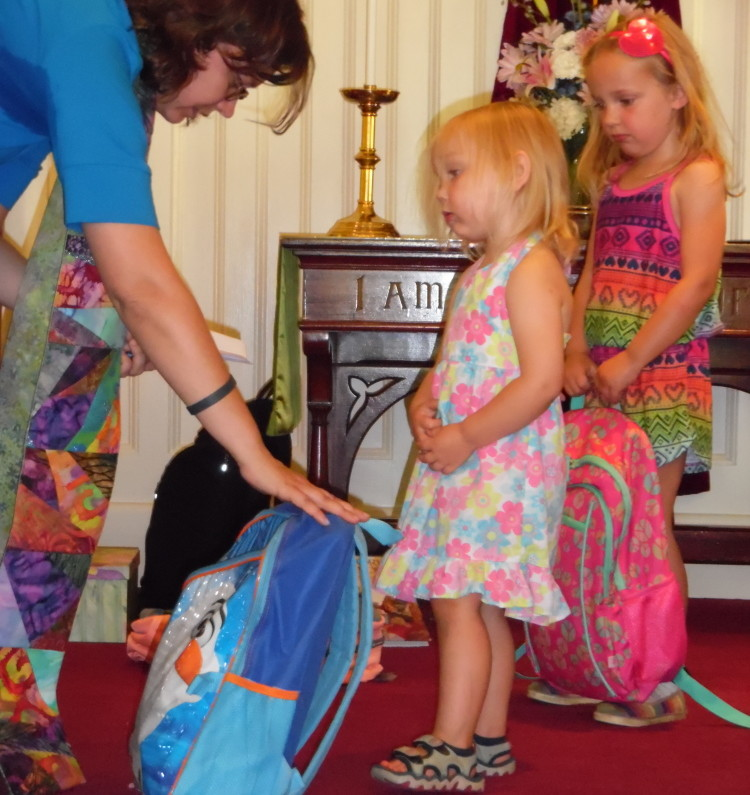 Winthrop Congregational Church Pastor Chrissy Cataldo blesses Alice Lazure's back pack while sister Gabby waits in the background. This is the second year Cataldo has blessed student and teachers' backpacks, laptops and lesson plans the Sunday before school returns to session.