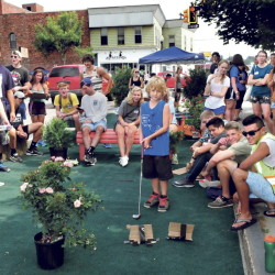 "Surrounded by Colby College students, Zachary Wentworth of Clinton, center, eyes his golf shot at the ""relaxation"" park set up in downtown Waterville as an orientation project by incoming students on Thursday. Student Andrew Destaebler raises his arm as the ball goes in. (Staff Photographer)"
