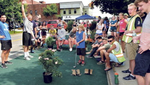 """Surrounded by Colby College students, Zachary Wentworth of Clinton, center, eyes his golf shot at the """"relaxation"""" park set up in downtown Waterville as an orientation project by incoming students on Thursday. Student Andrew Destaebler raises his arm as the ball goes in. (Staff Photographer)"""