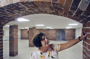 Gardiner Public Library Director Anne Davis inspects brick work Thursday in the recently renovated archivist room in the library's basement. A consultant's report recommended cutting the part-time archivist position and revising the formula for charging other member communities.