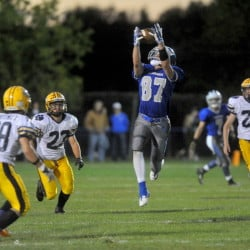 Staff file photo by Michael G. Seamans   Lawrence High School receiver Seth Powers (87) makes a catch between Mt. Blue defenders during a game last September in Farmington. Powers and the Bulldogs open their season Friday night at Skowhegan.