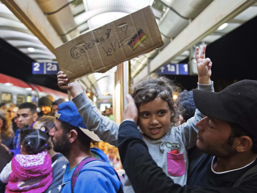 Refugees arrive at the train station in Saalfeld, central Germany, Saturday.