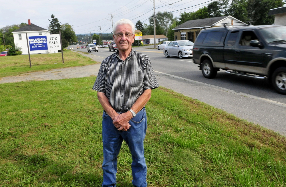 Leland Bard stands at his lot Thursday as traffic passes on Kennedy Memorial Drive in Waterville. Bard is having difficulty selling the land because of zoning restrictions.