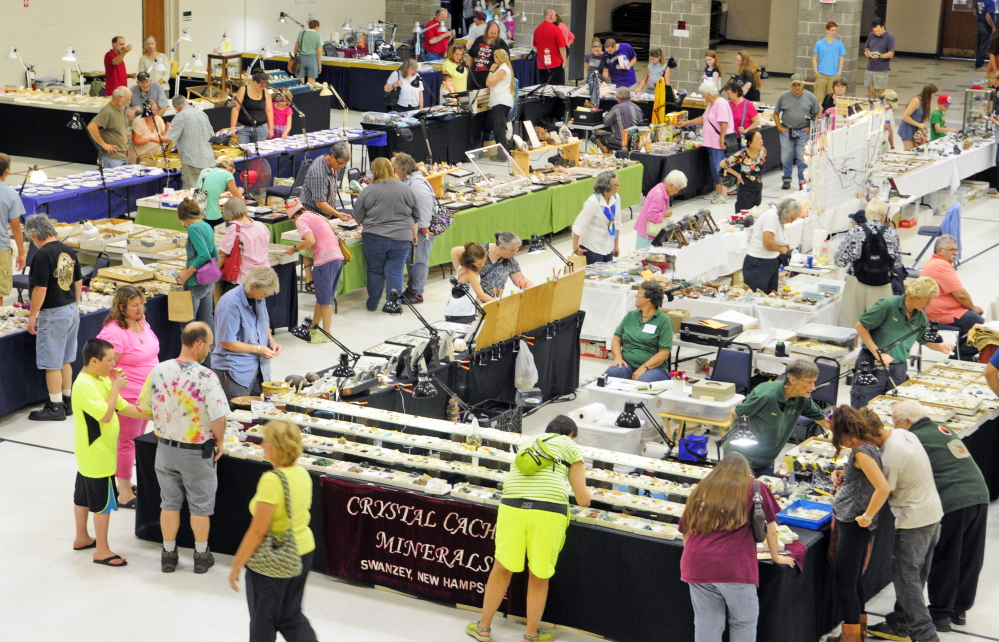 Staff photo by Joe Phelan People look over the displays Saturday during the Rockhounders 26th Annual Gem and Mineral Show at the Augusta State Armory.