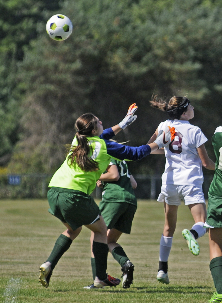 Rangeley keeper Sydney Royce, left, watches a header as Richmond's Meranda Martin arches over her and into the net during a game Saturday at Richmond High School. Richmond won 5-0.
