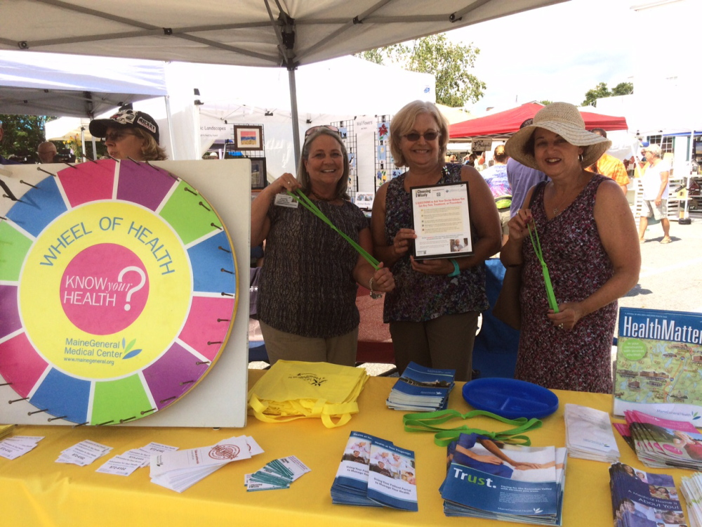 Dr. Lara Walsh, far left, of Winthrop Pediatrics, talks to festivalgoers Aug. 15 about the Wheel of Health while from left, Kathie Clark, Beth Corey-Smith, and Carol Cortes, all employees of Winthrop Family Medicine, show how to use exercise bands.
