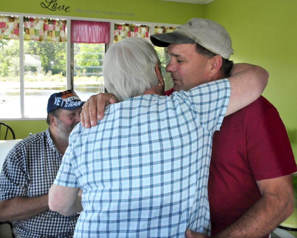 Diane Buckley gives Here's the Scoop co-owner Scott Stanchfield a congratulatory hug Friday on the first day in two years that the Bingham business has been open. The business was damaged by fire, and Stanchfield suffered serious injuries in March 2014 in a snowmobile accident.