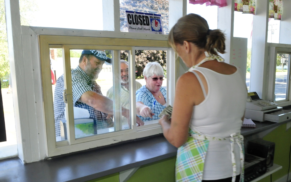 """Vicki Stanchfield serves ice cream Friday to Larry Buckley, left, as Dick Amidio and Diane Buckley wait for their desserts at Here's the Scoop in Bingham. Larry Buckley said he missed the store for the last two years and is glad the Stanchfields have reopened it. """"They are wonderful people,"""" he said."""