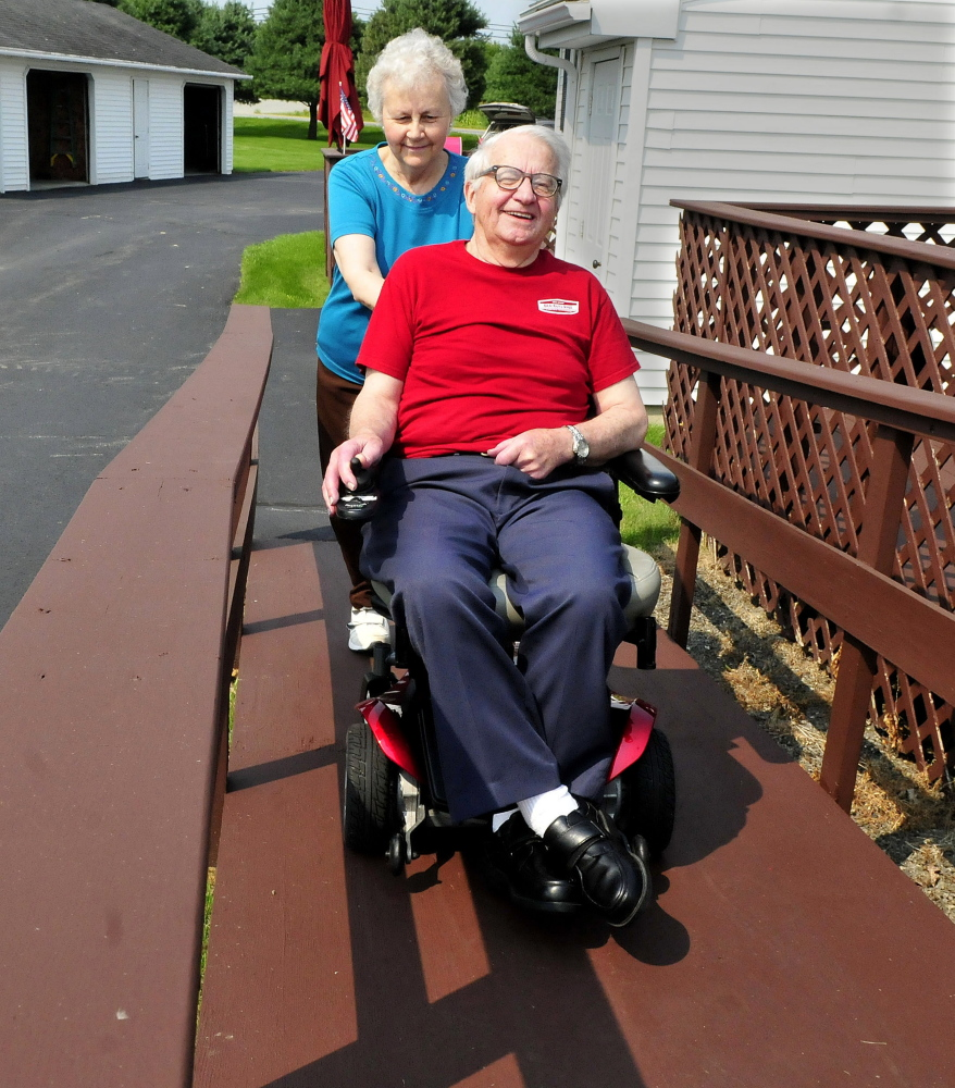 Larry Plourde makes his way up a wheelchair ramp as his wife, Noella, follows on Aug. 31 at their home in Winslow. Larry Plourde has cerebellar ataxia, which causes balance and mobility problems.
