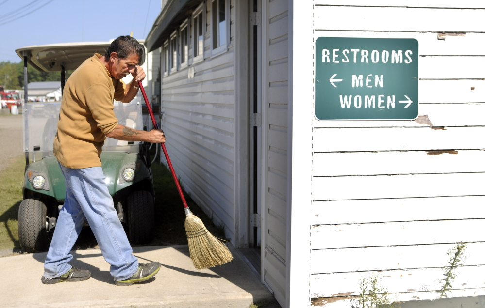 Edward Katz cleans a restroom Sunday at the Windsor Fair. Katz works several hours during the week of the fair, maintaining the facility for tips.