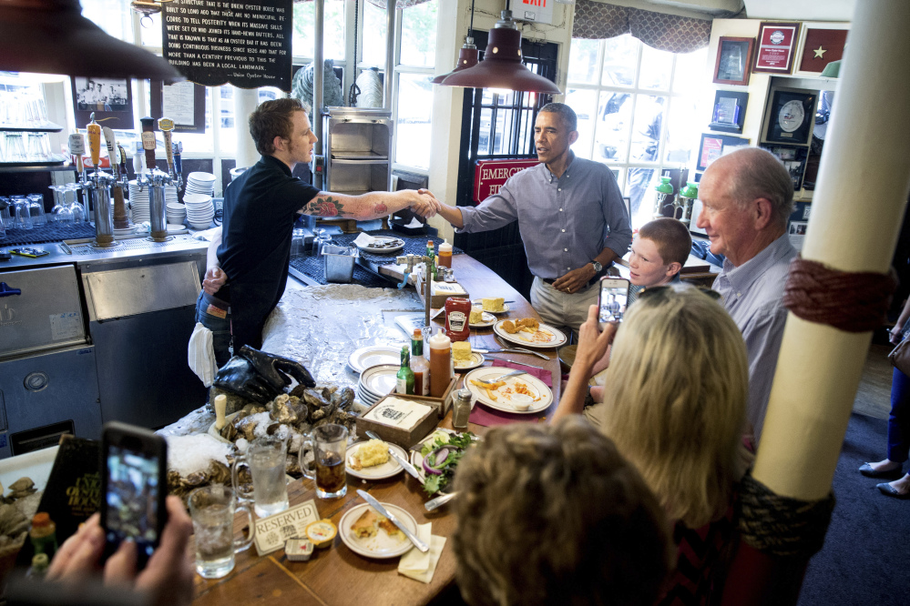 Greets people at Ye Olde Union Oyster House, Monday, Sept. 7, 2015, in Boson. Obama will sign an Executive Order requiring federal contractors to offer their employees up to seven days of paid sick leave per year. (AP Photo/Andrew Harnik)