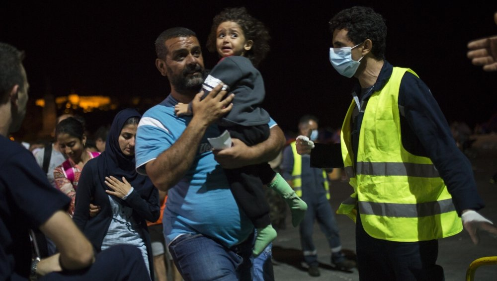 A Syrian man and his child board a ferry traveling to Athens, at the port of Lesbos Island, Greece, on Monday. The island of 100,000 residents has been transformed by the sudden new population of 20,000 migrants.