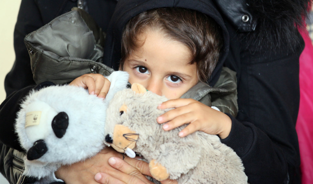 A migrant child holds cuddly toys at the Westbahnhof station in Vienna, Austria, Monday, Sept. 7.