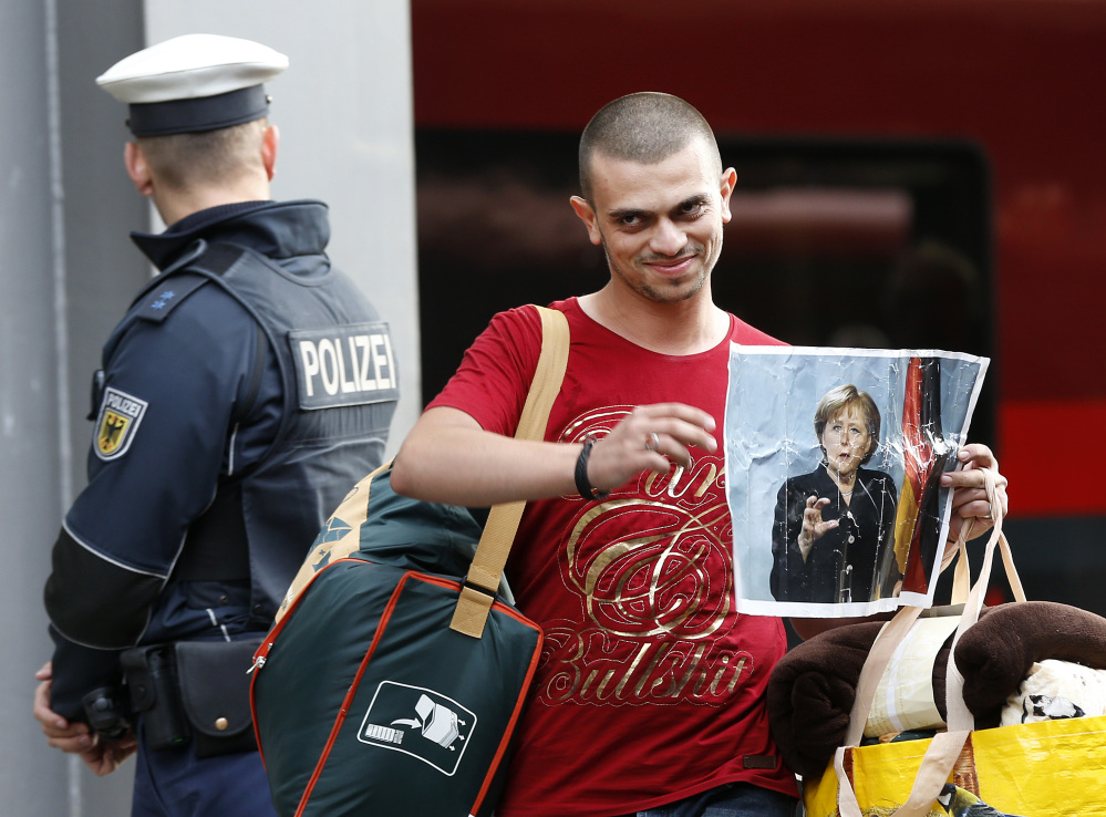 A refugee carries a picture of German Chancellor Angela Merkel as he arrives at the main train station in Munich, Germany, Saturday, Sept. 5. Hundreds of refugees arrived in various trains to get first registration as asylum seekers in Germany.